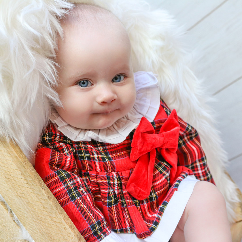 sweet baby girl wearing red tartan christmas outfit with big red bow and peter pan collar, lying down in a brown wooden crate stuffed with a white fluffy rug