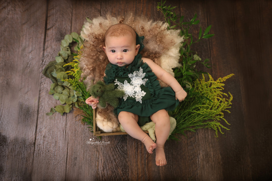 baby girl wearing green, lying in a wooden crate surrounded by flowers and greenery