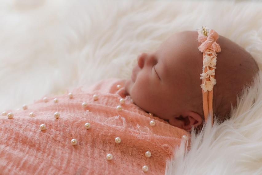 sleeping newborn girl in pink wearing pink headband