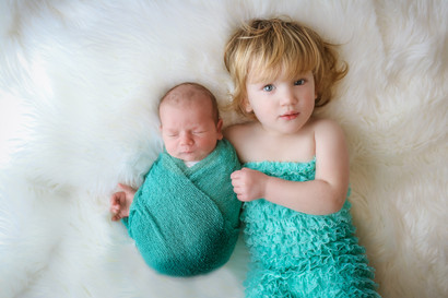 a toddler girl wearing a turquoise frilly romper, cuddling her newborn baby brother wearing a turquoise wrap, laying on a white furry rug