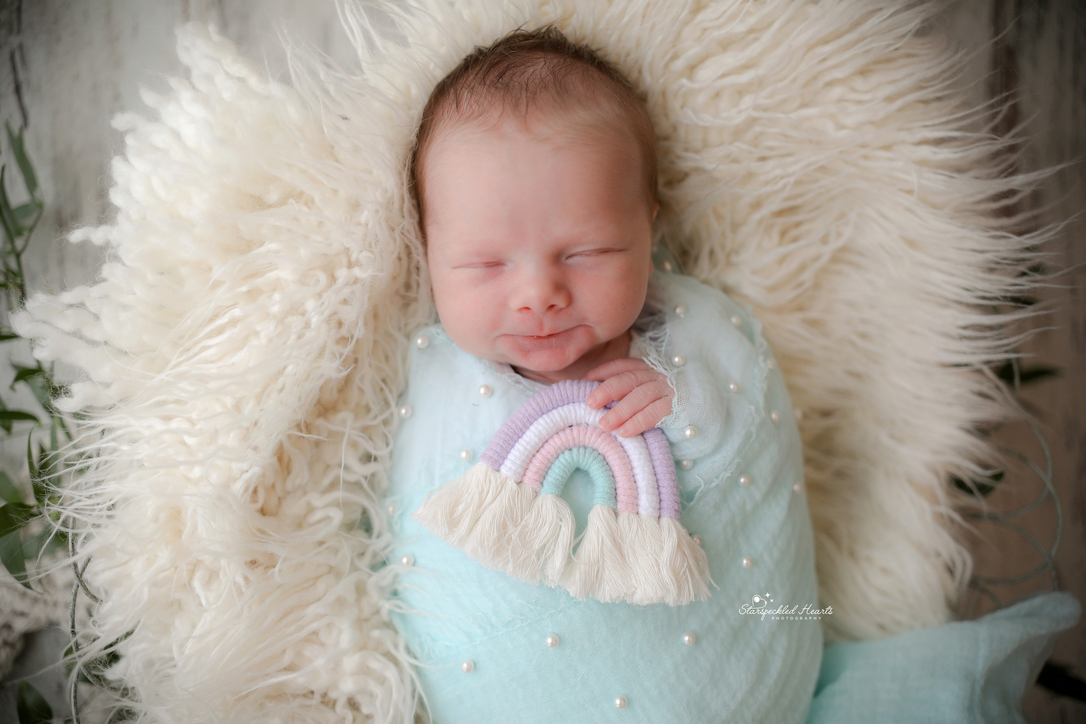 smiling newborn baby girl wrapped in blue holding a macrame rainbow
