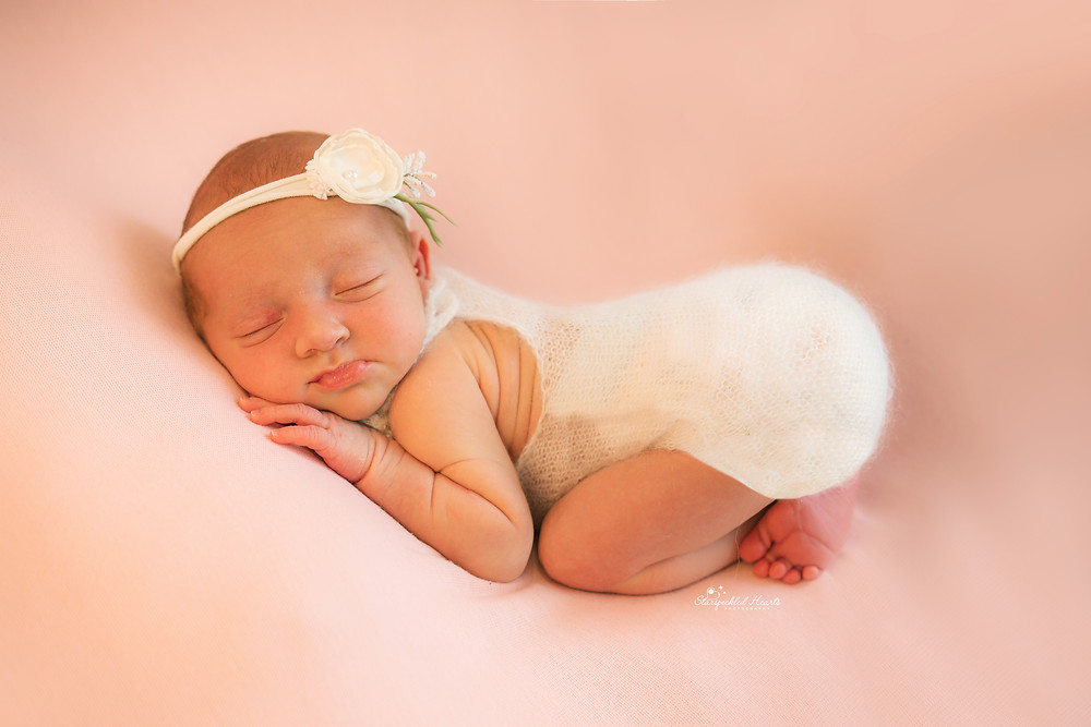 sweet newborn baby girl in the bum up pose, lying on a pink blanket