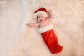 baby girl wearing a santa hat and lying inside a red christmas stocking on a white fluffy rug