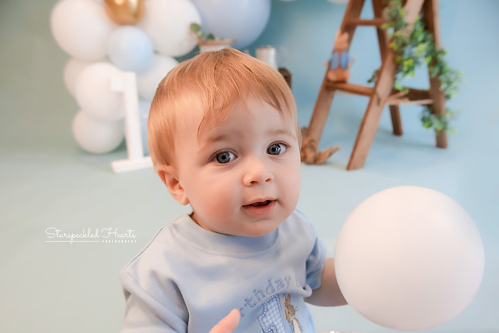 close up of baby boy with big blue eyes wearing a blue peter rabbit tshirt, cake smash photographer near me hampshire surrey
