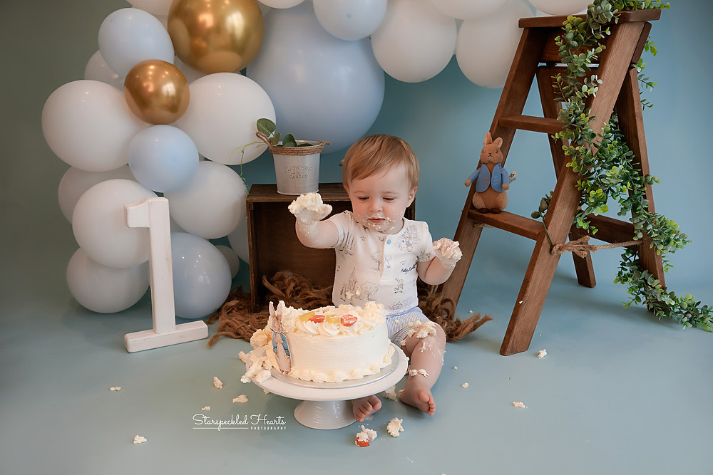 cake smash session in basingstoke, a little boy smashing up a large white cake on a blue background