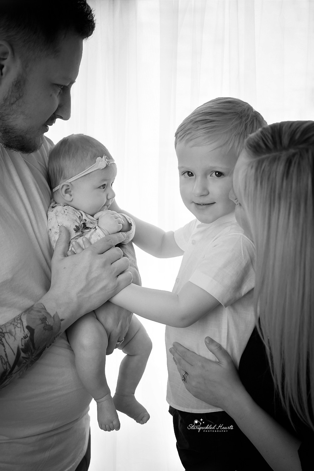 a family portrait focused on a big brother and baby sister for her newborn baby photography session