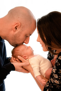 a profile shot of a mother and father looking down over their sleeping newborn son, the father giving his son a kiss on the forehead for their family photography session in hampshire berkshire surrey