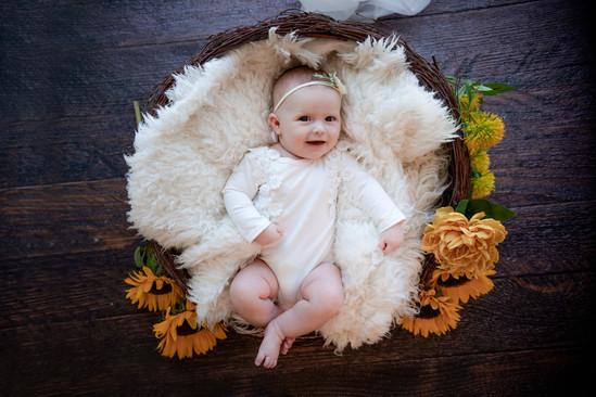 smiling baby girl lying in a wicker basket on a dark wooden floor