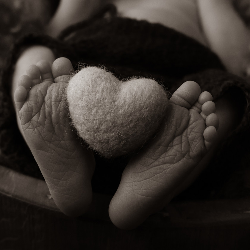 closeup of baby toes holding up a felted heart