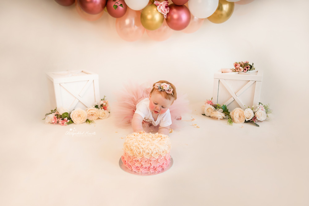 baby girl reaching out for her cake for her cake smash session with starspeckled hearts photography in aldershot hampshire