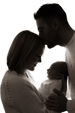 a man and woman wearing all white holding a newborn in their arms, woman gazing lovingly down at their baby whilst the man kisses her on the forehead, in black and white
