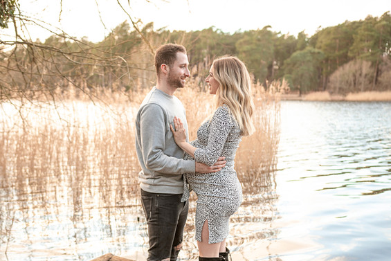 a pregnant woman and her husband in an embrace, standing near a large lake covered in reeds for their outdoor maternity session with starspeckled hearts photography in aldershot hampshire