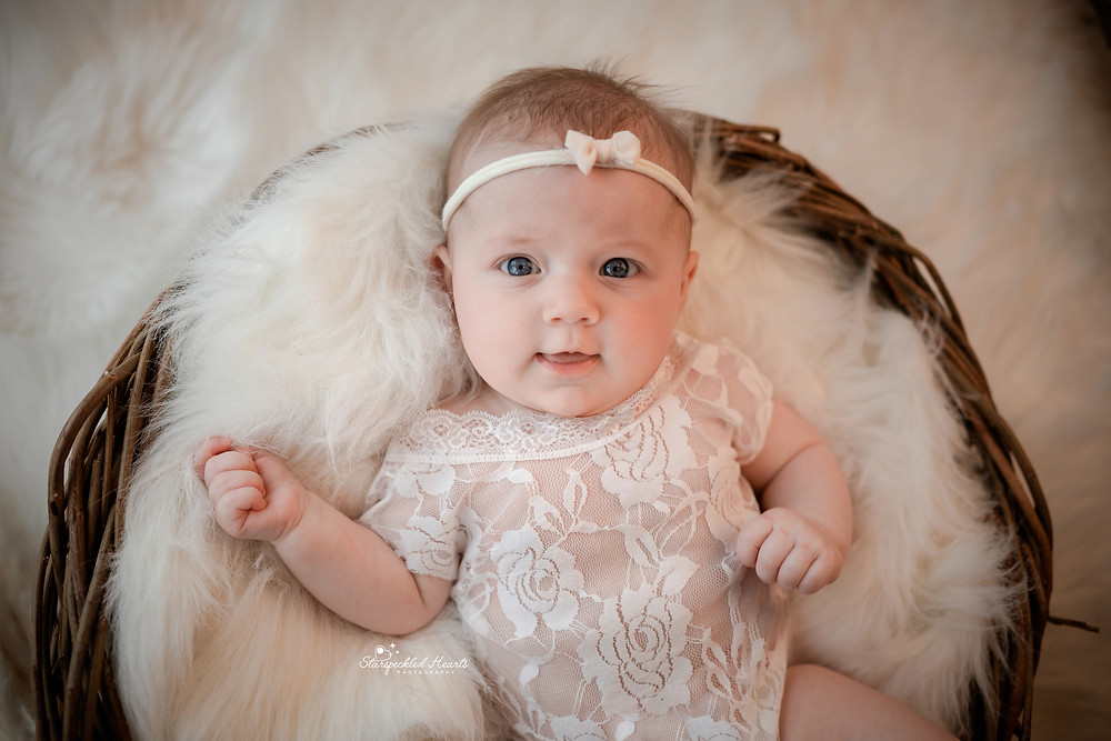 a smiling baby girl wearing a white lacy romper and matching headband, lying in a dark wicker basket for her newborn baby photography session in hampshire berkshire surrey