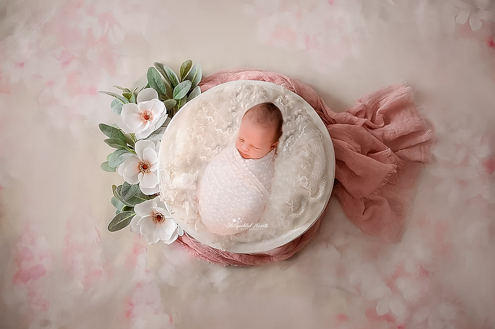 newborn lying in a bowl surrounded by flowers for her newborn session in aldershot hampshire