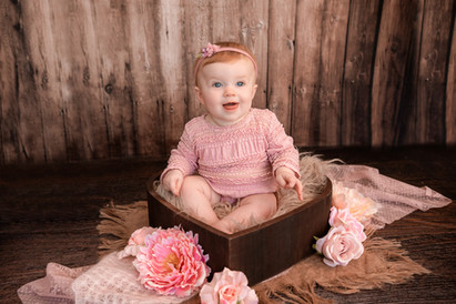 smiling baby girl sitting in a brown heart bowl surrounded by pink flowers