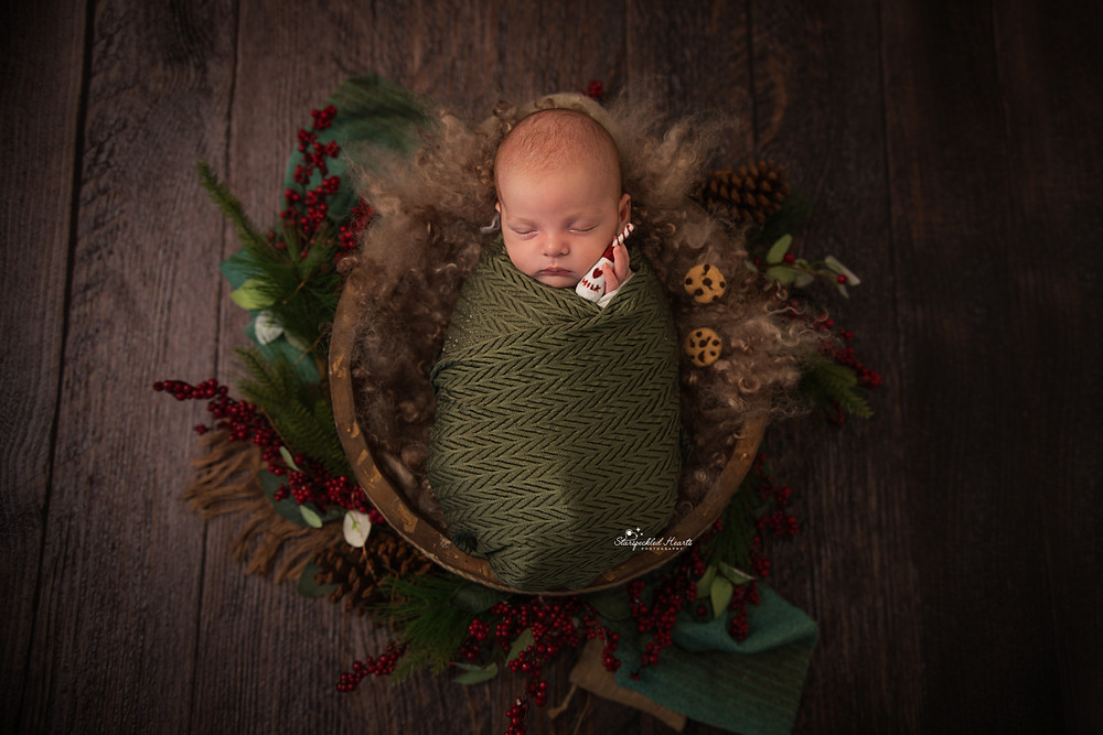 sleeping newborn baby boy wrapped in green holding a felt bottle of milk