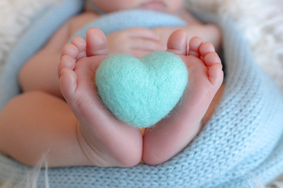 baby feet and toes curled around a turquoise felted heart