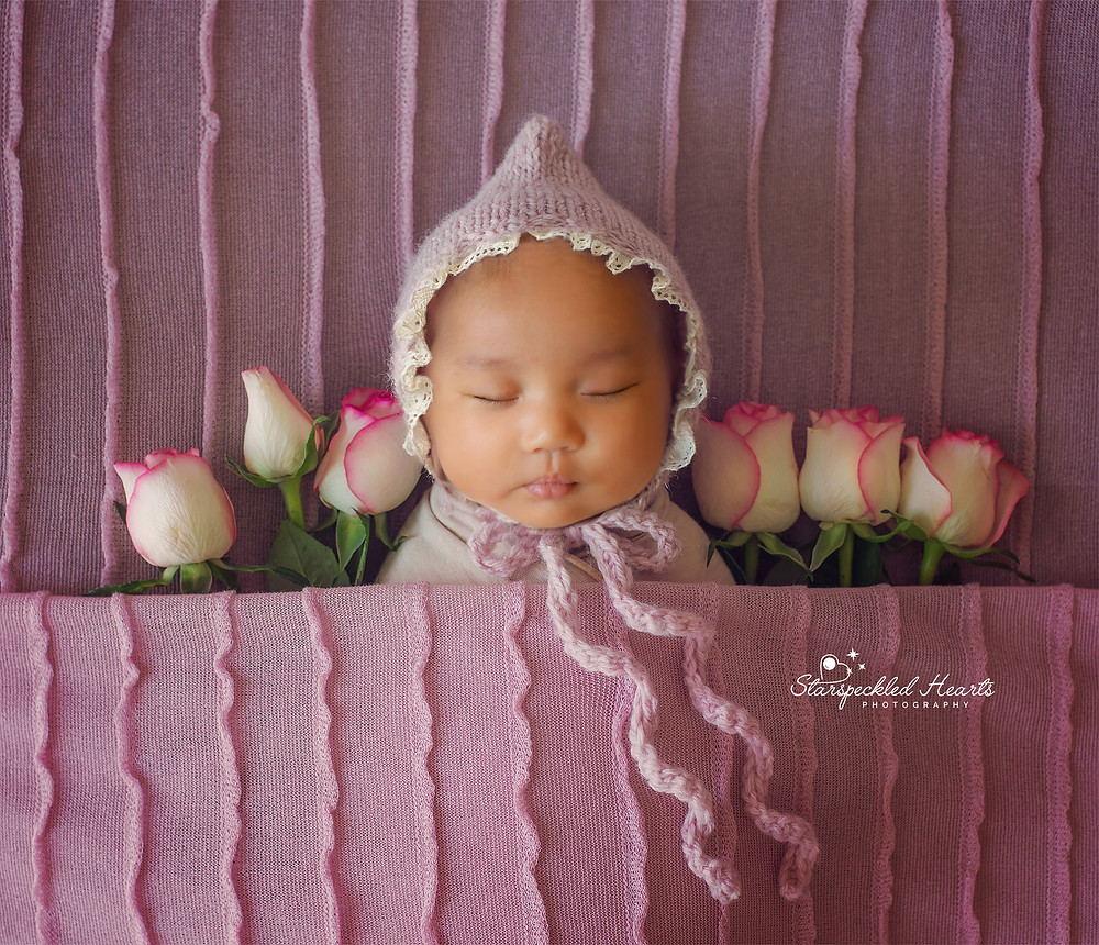 baby girl wearing a pink embroidered bonnet, laying next to roses