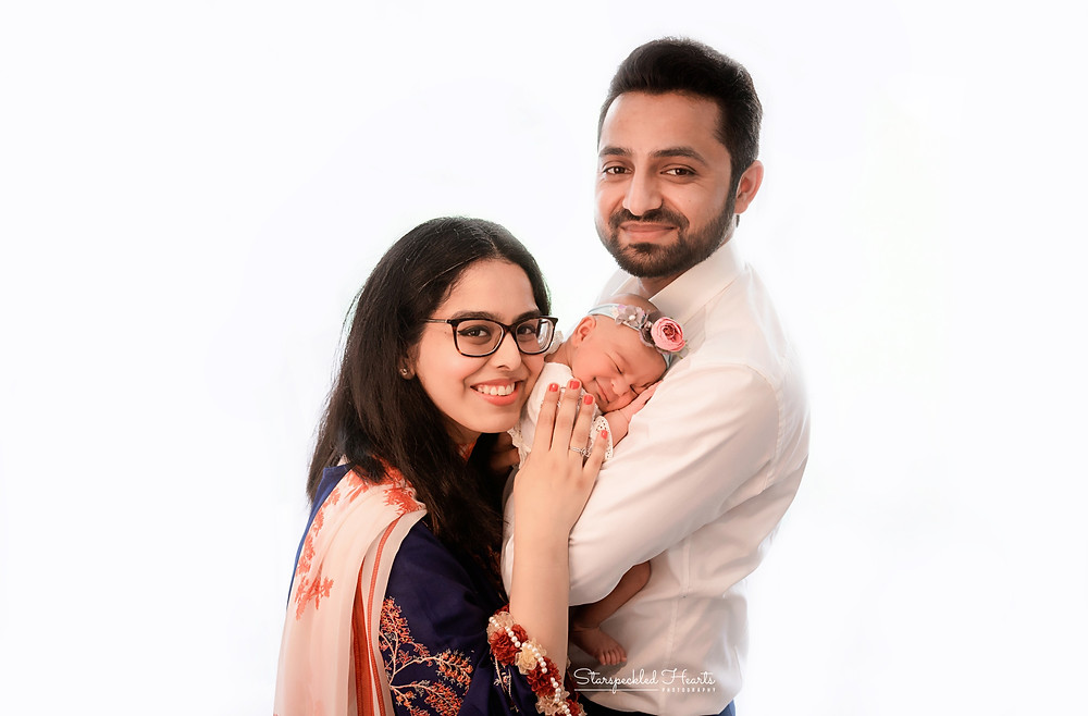 family portrait of a family of 3, cuddling their newborn baby girl for their newborn photography session in aldershot hampshire