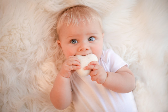 adorable baby boy with big blue eyes putting a large white felt heart in his mouth
