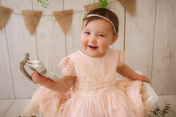 smiling gorgeous dark haired little girl, wearing a beautiful pale pink dress with lace embroidery, holding up a wooden toy horse, sitting on a curved wooden stool