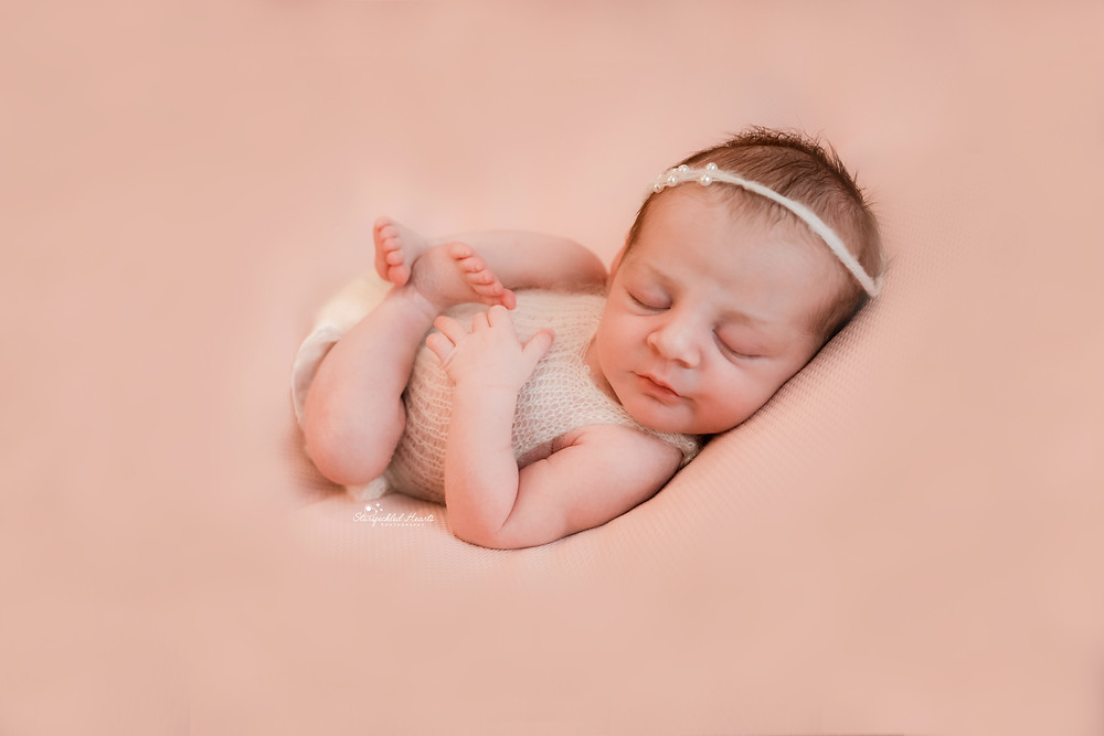newborn baby girl lying on her back, all curled up on the beanbag