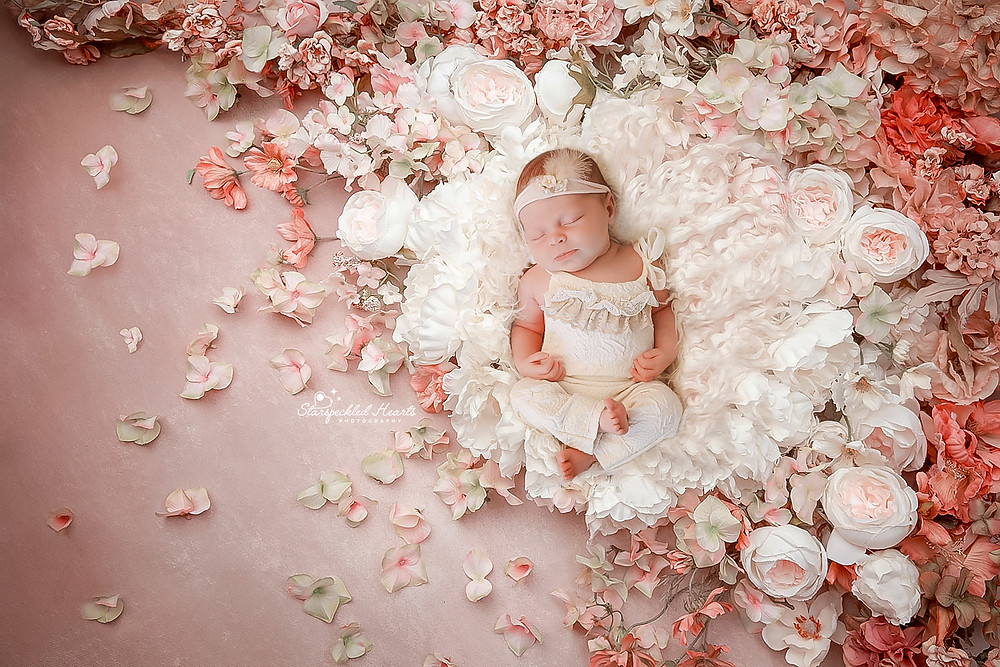 newborn baby girl lying on a fluffy white rug amongst flowers and flower petals for her newborn photography session in aldershot hampshire