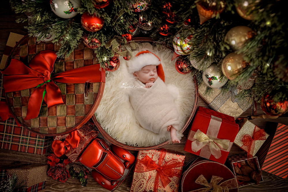 newborn baby christmas photo of baby boy wearing a santa hat, lying underneath a christmas tree in a box