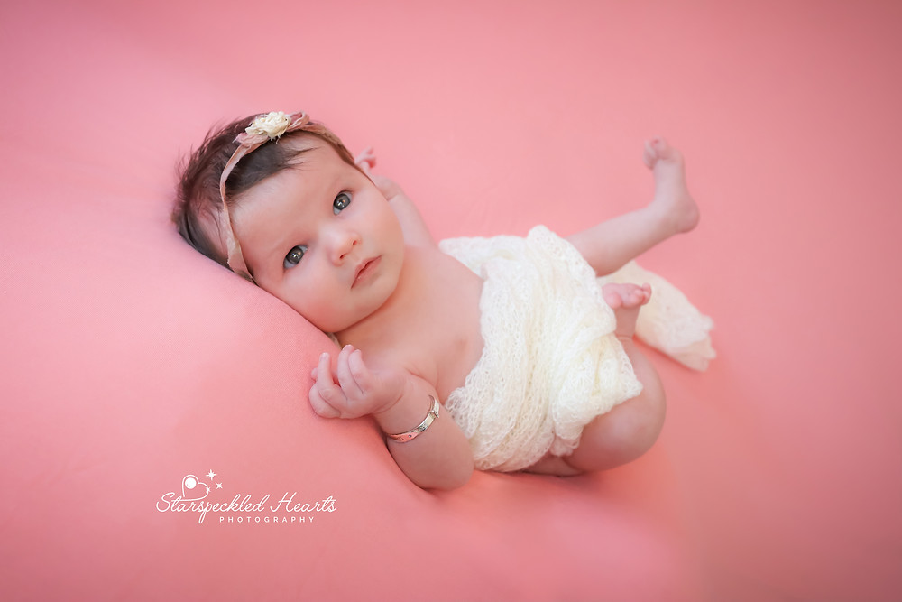 wide awake newborn on a pink background wrapped in white