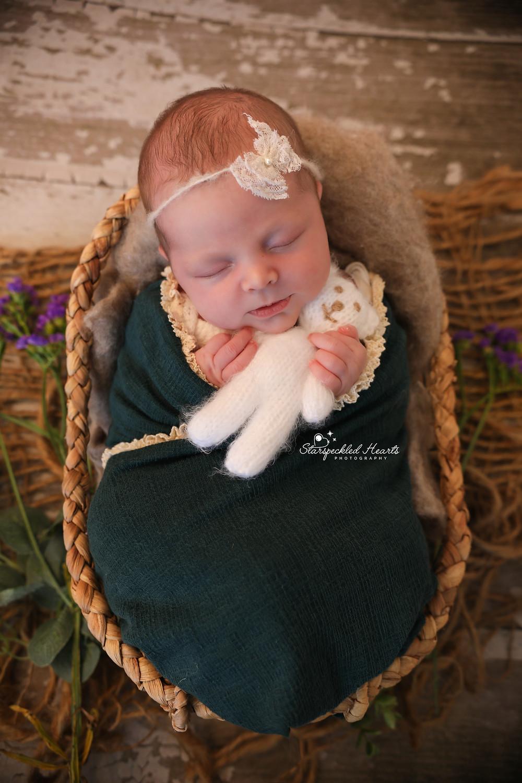 sleeping newborn wrapped in a green frilly wrap, cuddling a white teddy