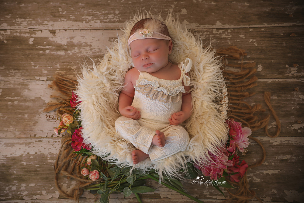 gorgeous sleeping baby girl laying in a white basket, surrounded by flowers