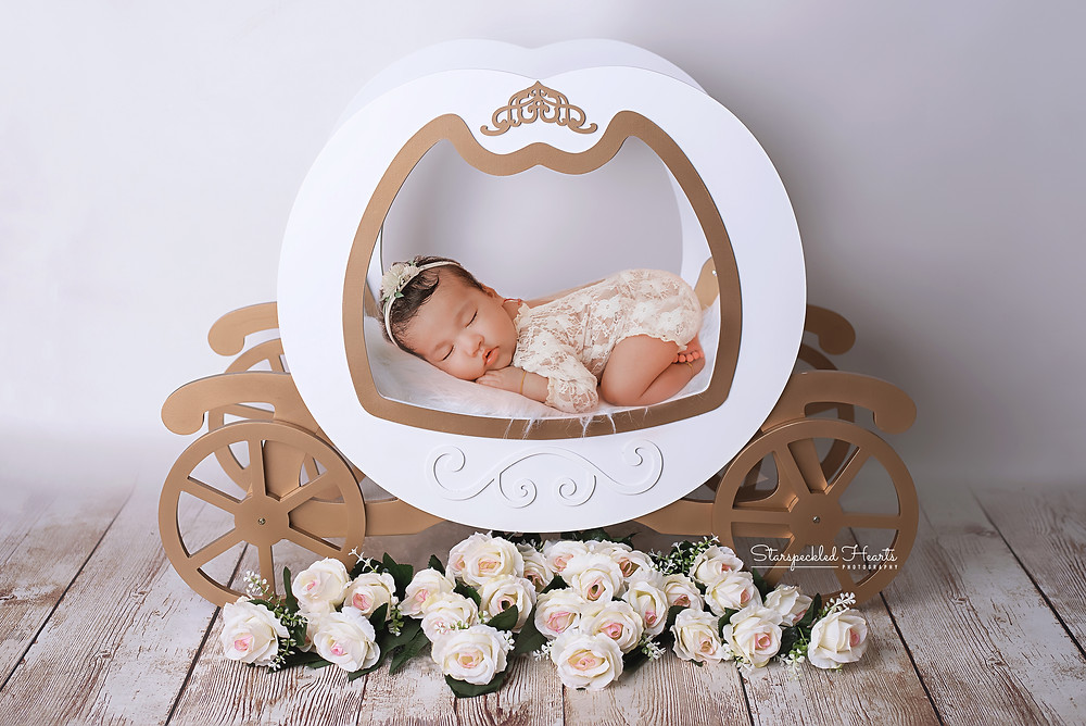sleeping newborn baby girl laying on her tummy in a princess carriage for her newborn photography session with starspeckled hearts photography in aldershot, hampshire