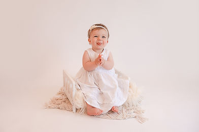 baby girl clapping her hands wearing a white dress for her photoshoot with starspeckled hearts photography in aldershot, hampshire