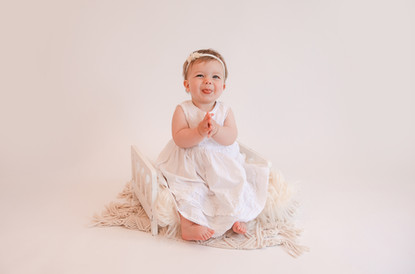 smiling baby girl wearing a white dress sitting on white bed at her baby photography session with starspeckled hearts photography