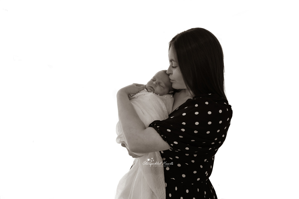 backlit image of mother holding her newborn baby girl up to her cheek, giving her a kiss