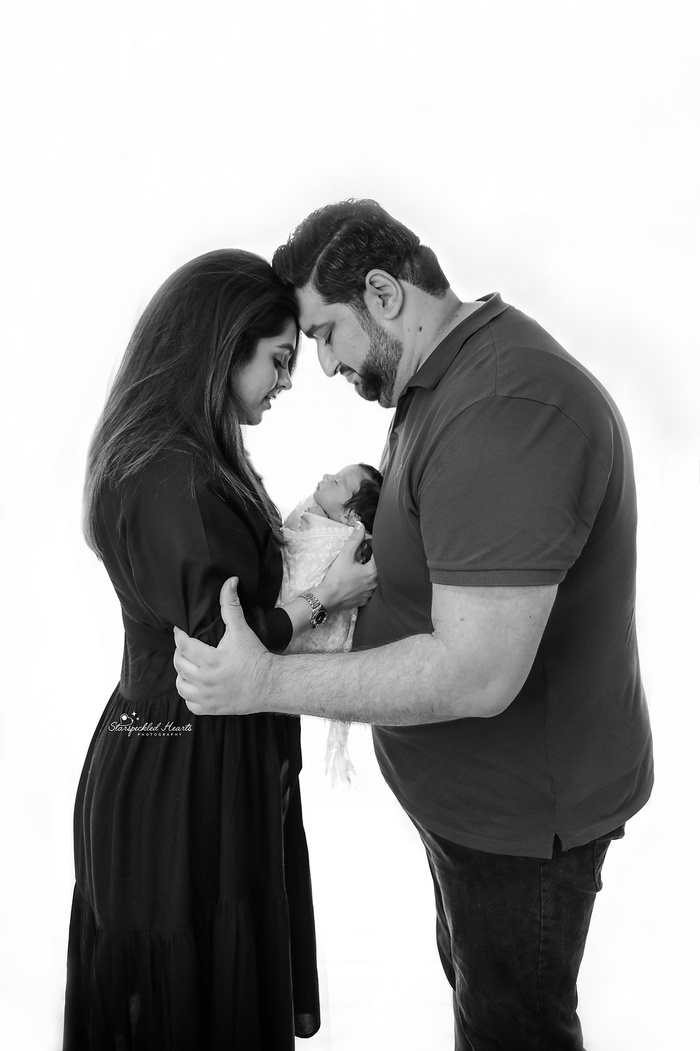family photo of a man, woman and newborn baby girl