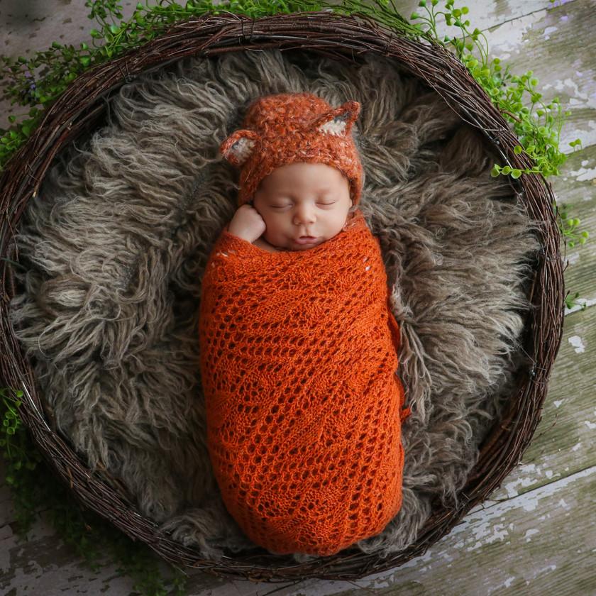 beautiful sleeping newborn wearing orange fox bonnet and wrap
