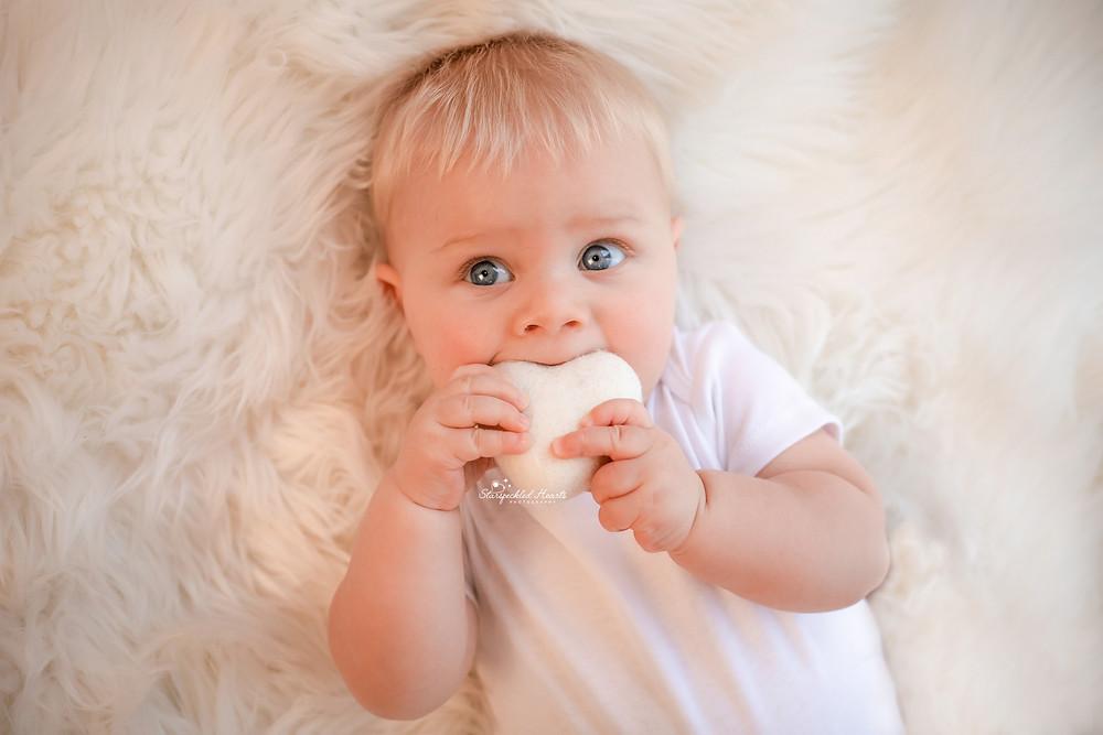 adorable blonde blue eyed baby boy biting  a white felt heart