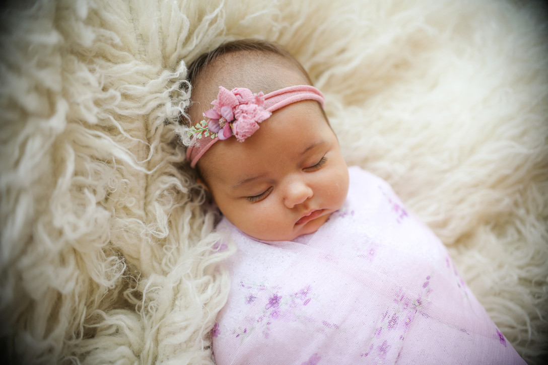 cute sleepy newborn wearing a lilac wrap and headband set lying on a white furry rug