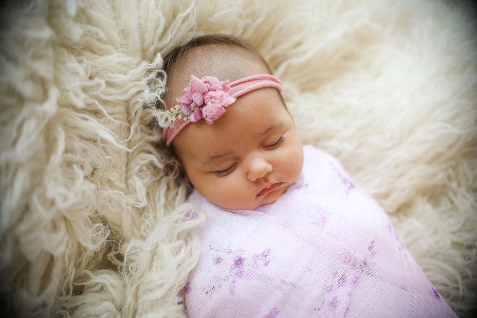 cute sleepy newborn wearing a lilac wrap and headband set lying on a white furry rug