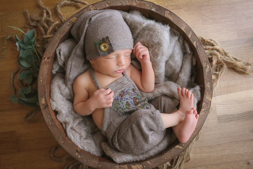 sleeping newborn wearing brown romper suit with matching sleepy hat, lying in a round dark brown wooden bowl