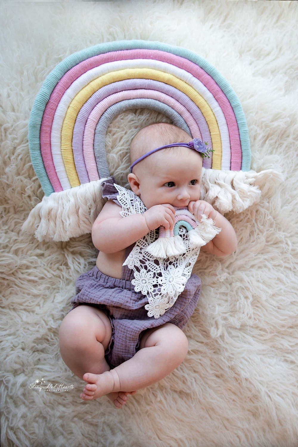 baby girl dressed in lilac lying on a white rug with a rainbow over her head