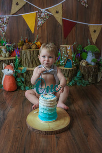 little boy eating birthday cake with his hands