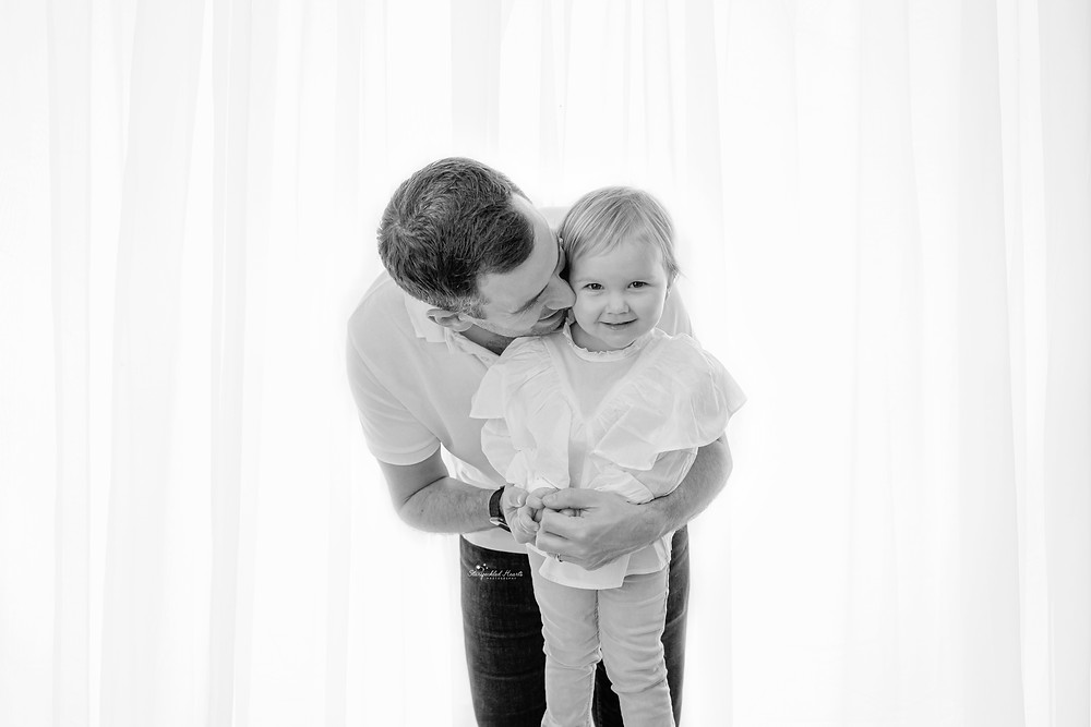 father holding his little girl around the waist, giving her a kiss on the cheek