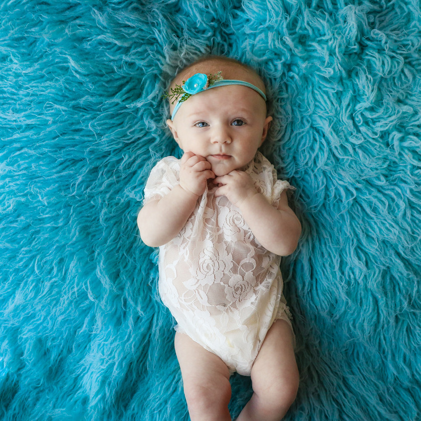 baby girl laying on bright blue rug wearing white lace romper