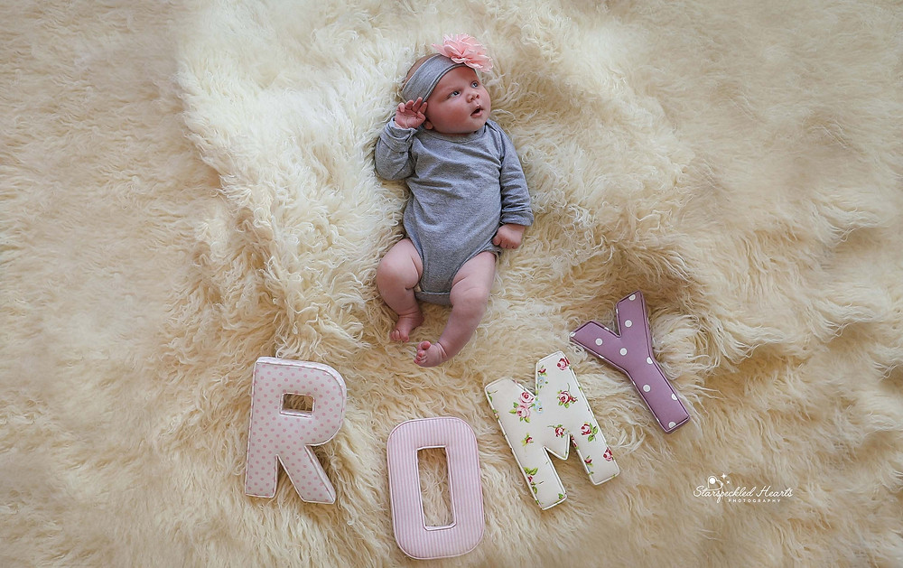 "baby girl wearing grey, lying on a white fluffy rug with large letters below her feet spelling out ""Romy"""