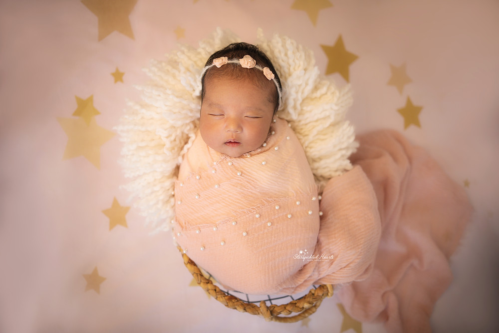 newborn baby girl wrapped in a pink pearl embellished wrap, lying in a basket on a pink and gold star backdrop for her newborn photography session with starspeckled hearts photography
