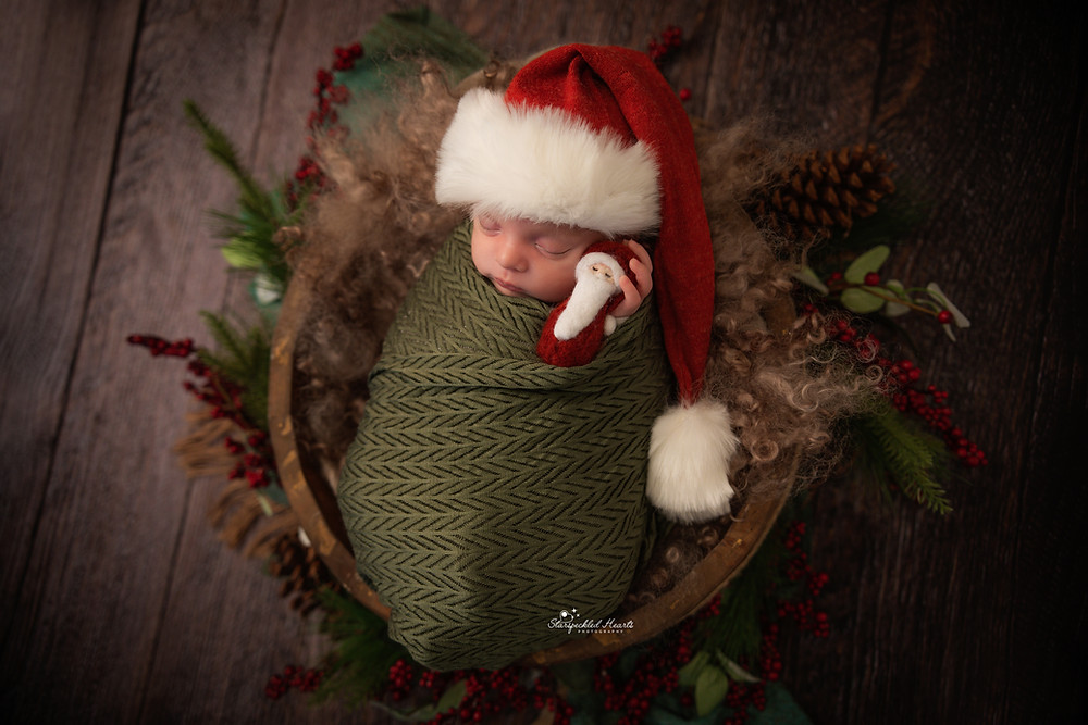 sleeping newborn swaddled in green and wearing a santa hat for his newborn session with starspeckled hearts photography in hampshire