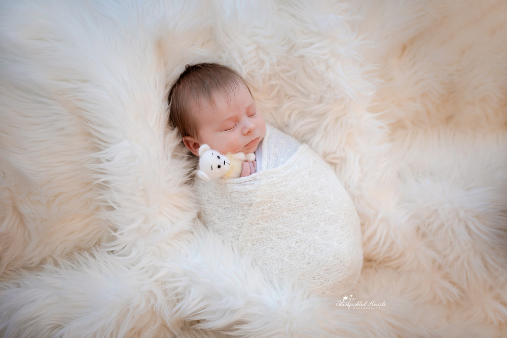 sleeping newborn wrapped up in a white textured blanket, lying on a white furry rug cuddling a white teddy for his newborn session with starspeckled hearts photography