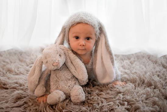 baby boy dressed in a grey knitted bunny outfit, cuddling a bunny teddy